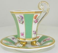 KPM Berlin porcelain cabinet cup and saucer with moulded handle and standing on three paw feet. Shaped cup and saucer with handpainted flowers on the panels . Printed marks to base