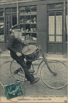 Old French postcard, man beating a drum on his tricycle.