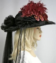 "Victorian Burgundy Black Hat: Victorian hat accented with pansies & a large rose. Straw hat base in black with a black satin crown. Trimmed all around in black floral lace & a black tulle train is gathered, & hangs down about 36""."