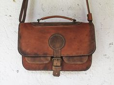 This Antiqued Brown Leather Satchel Bag features:  ★ Handcrafted in authentic cow leather ★ Tanned in light brown leather color ★ Genuine Iron Hardware ★ Leather buckle closure Main Compartment ★ 2 front exterior leather pockets with metal fasteners ★ Leather Carry Handle ★ Adjustable Leather shoulder strap ★ One Large Leather Interior compartment ★ One Interior zipper closing pocket measuring 20 cm / 7.87 in ★ One Interior phone pocket measuring 14 x 8 cm / 5.5 x 3.14 in ★ Interior leather…