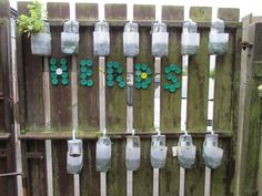 Herb fence, with the word 'herbs' displayed in milk bottle tops!