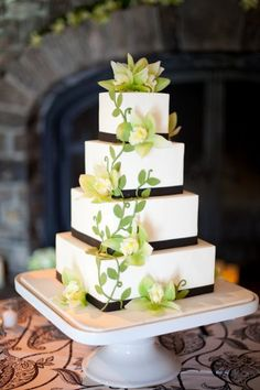White cake with brown ribbon detail and white/yellow flowers on vine.