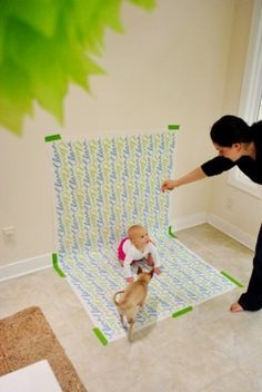 DIY backdrop with wrapping paper great idea for taking baby pictures and you can change it up with different out fits on the same day when baby is happy !