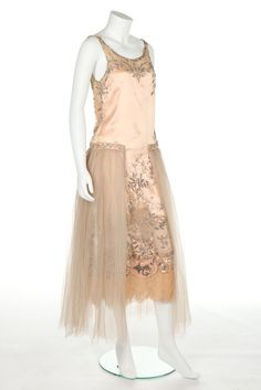 A couture beaded satin gown, possibly Patou, circa 1922-4, the above ankle pink satin column lavishly adorned with pearl beads, rhinestones, with chiffon inserts to bodice front, sides, and skirt giving glimpses of the knees, tulle floating panels to the sides, bust 81cm, 32in