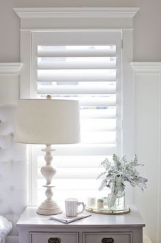 Beautiful white plantation shutters in a bedroom above a nightstand with lamp.