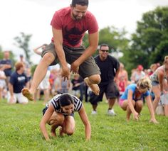 Daniel Ghiringhelli of Catonsville gets air as he leaps over his wife Jenniffer on their way to winning the adult leap frog race during the annual Independence Day games at Catonsville High School. (Brian Krista/Baltimore Sun Media Group)