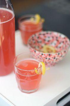 Pink Punch: 1 750 ml. bottle dry champagne 1 12 oz. can frozen lemonade concentrate 6 oz. St. Germain 6 oz. cranberry juice 2 tablespoons superfine sugar, optional lemon slices or curls for garnish