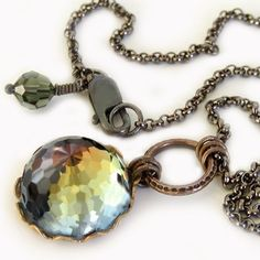 This striking crystal is set in vintage natural brass with a pretty scalloped edge and dangles from a textured brass ring. Petite gunmetal rolo chain is finished with a gunmetal clasp and a sparkling Swarovski crystal bead. MEMBER - jQjewelrydesigns