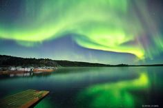 A neon green aurora is reflected in the waters off Yellowknife, Canada, in a newly released picture.