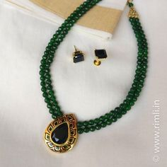 A short neckpiece with two layer green agate beads paired with a meenakari locket with a black stone, matched with a black square earstud.Available at Rimli Boutique, T Nagar, Chennai.
