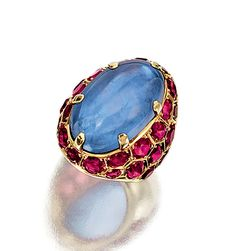 SAPPHIRE AND RUBY RING, SUZANNE BELPERRON,  1950S.  The cabochon sapphire highlighted with oval and circular-cut ruby surrounds, mounted in yellow gold,  French assay and maker's marks.  size 52,