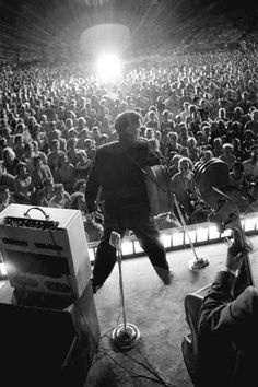 """Starburst """"Flashbulbs were going off constantly. When I developed the film, I discovered a shot of Elvis with a magnificent spray of light in front of him. Not strong enough to reach the stage, the flash highlighted the back of about thirty rows of heads as well. That random flash was in perfect sync with my shutter opening. That photograph, represented for me this entire experience and was better than anything I had done previously or would do. This unexpected lucky moment gave me…"""
