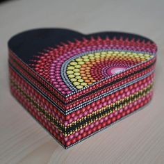 This beautifully hand-painted mandala dot art jewellery box / trinket box is from the French Riviera. It is shaped in a heart and carefully painted using dot art. It is painted all black, with detailing in a mix of colours; pink, red, orange, yellow and silver, finished with a lighter