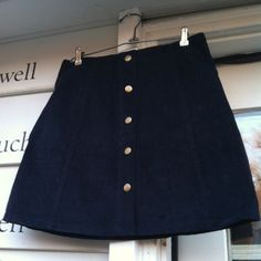 "NWT Navy Corduroy Button Front A-Line Mini Skirt Super cute new with tags high-waisted corduroy skirt.  It's labeled a US size 8.  It's meant to be high-waisted so the waist would be smaller than if you wore it on your hip, but I still found it to run small. So if interested in purchasing, please go by the following measurements.  There is no stretch. Measurements laying flat:  Waist:  15""   Length:  16 1/2""   Snap metal buttons down the front. Topshop Skirts Mini"