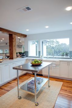 The new modern kitchen features white cabinets, exposed wood beams, great views and lots of light. The island with stainless top and casters provides additional prep space and flexibility.