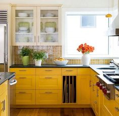 yellow kitchen cabinets, two color kitchen, yellow pattern tile backsplash, black kitchen counters