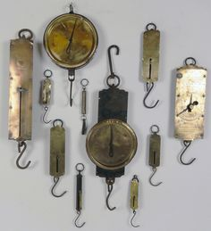 A collection of 11 antique hanging brass milk scales