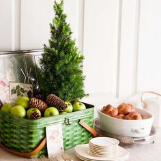 Add to the holiday cheer of your party table with a tabletop Christmas tree in a green picnic tin. Fill the container with apples, oranges, or other fruits, top with pinecones, and use the decoration to mark the start of your buffet line. Christmas Buffet, Tabletop Christmas Tree, Christmas Tablescapes, Mini Christmas Tree, Christmas Holidays, Christmas Decorations, Holiday Decorating, Merry Christmas, Winter Holiday