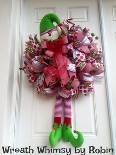 Deco Mesh Holiday Wreath with Elf Head and Legs.  This whimsical holiday wreath is bright, playful and so much fun! The wreath is constructed with a Premium foil deco mesh in a red, green & white stripe. The Elf elements are top quality plush and are so cute. The head measures 12 inches x 9 inches, the legs with adorable elf feet are 18 inches long and the feet stick out 8 inches. Surrounding the wreath are 32 festive ribbon streamers including a red/white canvas stripe, a large red/white…