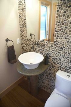 A powder room focuses on green sustainable design:- A dual flush toilet conserves water. Bamboo flooring is a renewable grass. River pebbles on the wall are a natural material. The sink pedestal is fashioned from salvaged wood from a 200 yr...