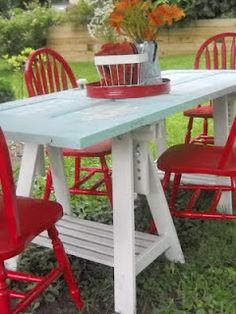 Door to table -- repurposed door, painted thrift store chairs, recycled Ikea sawhorses = new picnic table.  Love it!