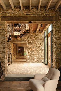 A two-story skylit entry hall announces the public entrance. A two-story skylit entry hall announces the public entrance. Slicing through the house from front to back, the atrium ho. Architecture Design, Stone Interior, Interior Ideas, Interior Design, Interior Walls, Interior Shutters, Open Staircase, Brick And Stone, Stone Walls