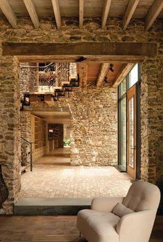 Un hall de entrada de luz natural de dos pisos, anuncia la entrada del público. Cortando a través de la casa de adelante hacia atrás, el interior hay una escalera abierta y el puente que conduce a los dormitorios del segundo piso. El salón está a la derecha; cocina y naranjos a la izquierda.