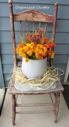 A weathered and chippy old dining chair with an enamelware pail of faux flowers.  Also use a little raffia to fall vignettes.