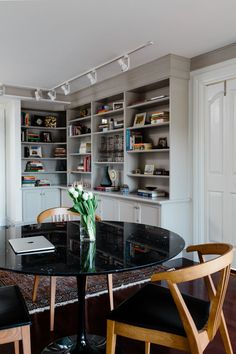In the study, the walnut shelving was updated with a light gray trim. The conference table was swapped out for a Saarinen tulip table with a striking black marble top.
