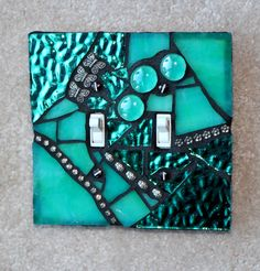 Double switch wall plate in green/turquoise foiled mirror glass and stained glass with turquoise and green swirls. Similar to Emerald Elegance but