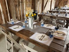Farm wood table with place mats, mason jars, silver material with tea light candles and watering can with florals