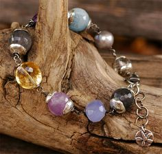 ~Mood Swings...  Beautiful gemstones capped in sterling silver! The gemstone line-up includes... Cloud Quartz! Lavender Amethyst, Citrine, Deep Amethyst, Freshwater Pearl, Holley Blue Chalcedony, Aquamarine and a clear Rutilated Quartz with black rutiles. Bracelet is adjustable from 7.25 to 8.0""