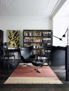 Bücherregal mit dunklen Möbeln - Schwarzes Holz farbiger Teppich - Egg Chair in schwarzem Leder
