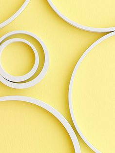 A little paint and fun embellishments work wonders without permanency. Paintable wooden rings in white pop out on top of a butter yellow wall, though any color combination could add a vibrant touch, even in an apartment or dorm room.