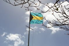 Flag of the Bahamas.  The two aquamarine stripes at the top and the bottom of the flag represent the sea and the sky, the gold stripe in the middle represents the sun and the black triangle represents the strength and unity of the people of the Bahamas.
