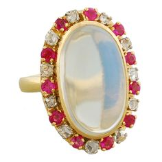 Victorian ring, ca 1880: a large cabochon moonstone, surrounded by 22 alternating rubies and old rose-cut diamonds, set in 18K gold