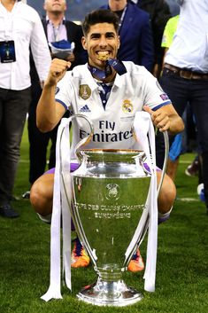 Marco Asensio of Real Madrid poses with the trophy following the UEFA...