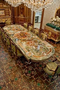 Gran dinning table with inlayed marble top, Green Forrest marble, carved legs with gold leaf, bronz detail.