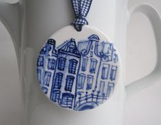Delft Blue Handpainted Porcelain Ornament | HarrietDamave, on Etsy. Love the handpainted scene depicting Dutch canal houses and the gingham checked grosgrain ribbon. So adorable!