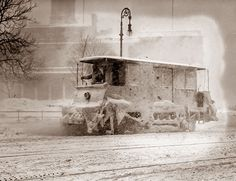 This picture of a winter storm in New York was taken in 1910. The vehicle looks like some sort of trolley.