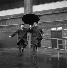 West Ham's Johnny Byrne and Bobby Moore singing in the rain at Upton Park in December, 1963