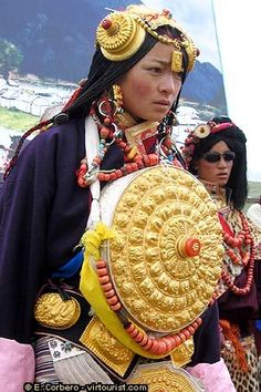 Tibetan festive costume. big gold box on her chest - box for amulets .