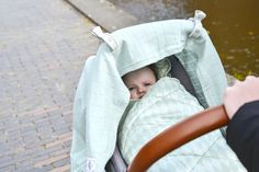 Forrest green Mini-Bunker in group 0+ carseat. with matching Solid Feather Swaddler and Swaddle-clips in grey Mist. www.lodger.com