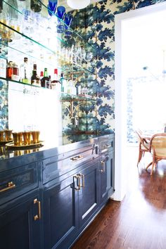 Patterned wallpaper in home bar with glass shelves displaying booze