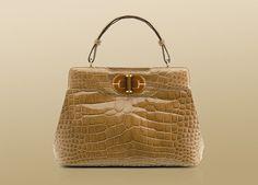 isabella handbag in shiny camel alligator with light gold plated hardware. caramel enamel closure with yellow tiger's eye twist lock...