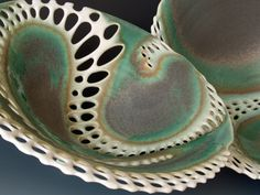 Two pierced bowls in porcelain with green grey glaze