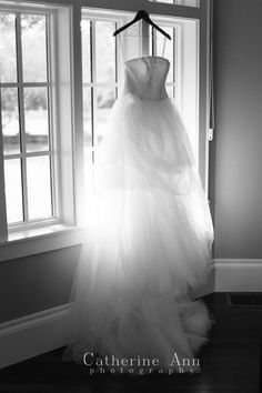 Backlit wedding dress hanging in front of window. We can get this shot in the parlor or bedroom in the morning.