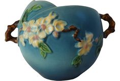 """Released in 1948 the """"Apple Blossom"""" line is a favorite among Roseville Pottery collectors that find the twig handles an attractive and unique design element. This 6.5"""" jardiniere comes from a crisp mold with precise painting. There is minimal crazing. The vase is bottom marked in relief """"Roseville U.S.A. 342-6""""."""