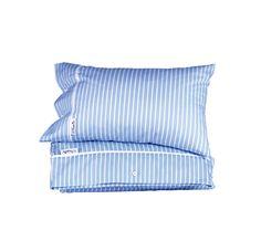 Ljusblå och vit pinstripe design med vit piping och dekorativa gummiknappar. Tillverkad i 100% twill bomull.