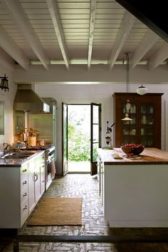 white kitchen butcher block island brick floor french doors Oh!  Photographer Jean Longpré's country house!